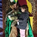 El Heraldo Real atiende a una niña durante su visita a El Palo